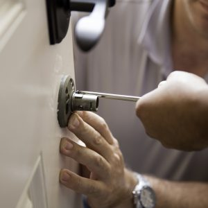 Locksmith working to unlock white residential door